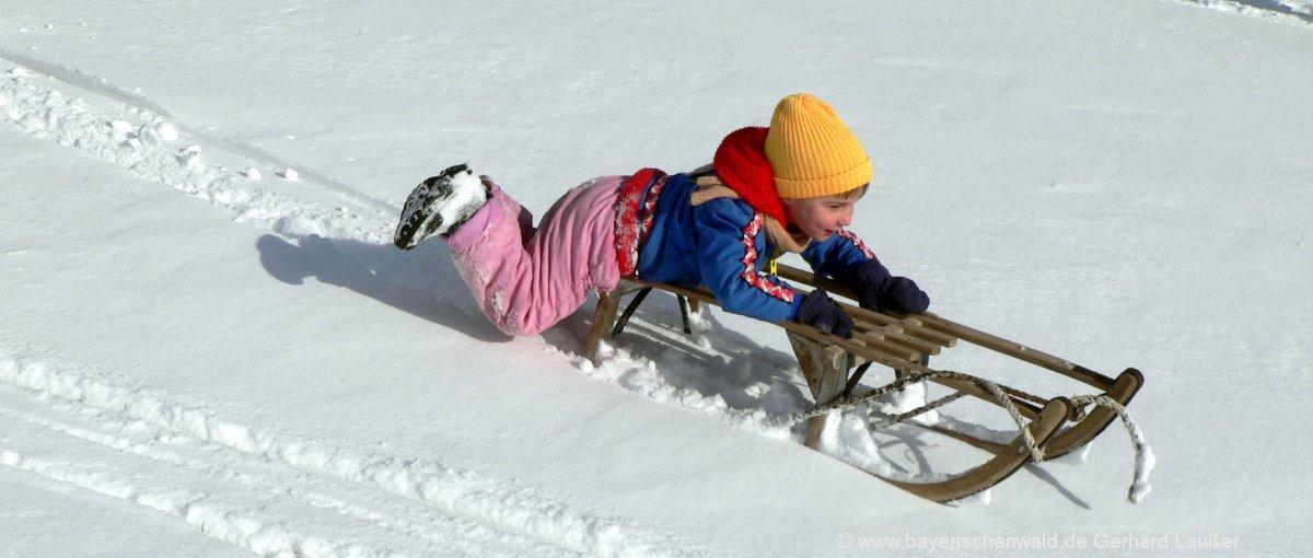 Bayerischer Wald Skiurlaub Familie mit Kindern schlittenfahren im Schnee